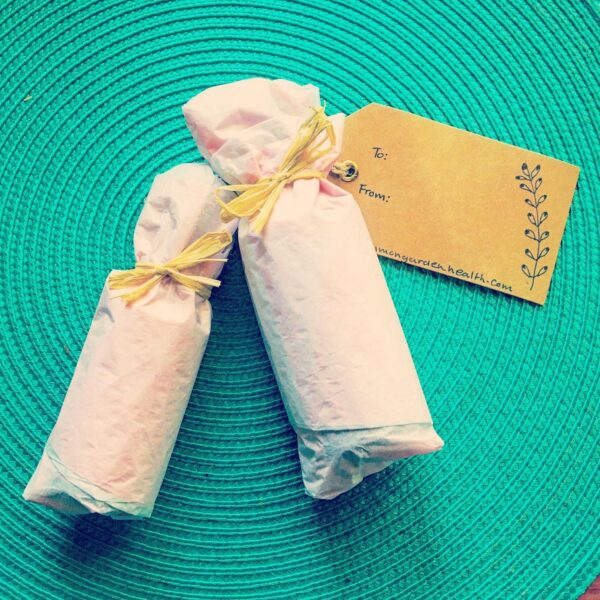 bottles wrapped in light pink tissue paper and tied with raffia. Recycled paper gift card with botanical illustration detail. Turquoise background