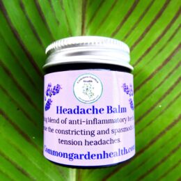 plant based headache balm in glass jar with silver lid on canna leaf background