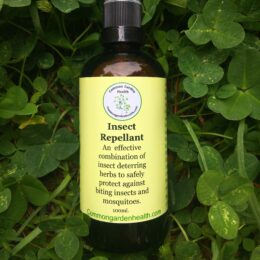 all natural insect repellent in glass bottle lying on grass